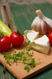 Two slices of camembert and vegetable on chopping board Royalty Free Stock Photography