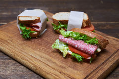 Two slices of lettuce and bread, one of sausage and tomato wrapp Royalty Free Stock Images