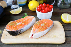 Two slices of salmon steak on a blackboard Stock Images