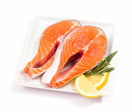 Two slices of salmon steak with herbs. Two slices of salmon steak with lemon and herbs Royalty Free Stock Photos