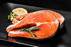Two slices of salmon steak with lemon. And herbs on black Royalty Free Stock Image