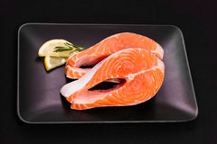 Two slices of salmon steak with lemon. And rosemary on black, top view Stock Photos