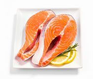 Two slices of salmon steak with lemon. And rosemary on white, top view Stock Images
