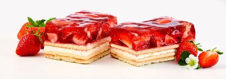 Two slices of strawberry and cream layer cake. Or tart topped with fresh ripe fruit in a syrup in a panorama banner on white royalty free stock image