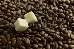 Two slices of sugar on a background of coffee beans Royalty Free Stock Photo