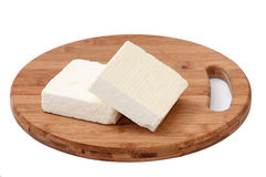Two slices of white feta cheese on a kitchen board Stock Image