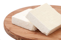 Two slices of white feta cheese on a kitchen board Royalty Free Stock Photo