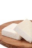Two slices of white feta cheese on a kitchen board Stock Photo