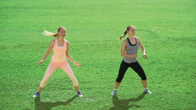 Two slim athletic women doing exercises on green grass stock footage