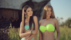 Two slim girls dressed in bikini and jewelry. Posing in field next to a small artificial waterfall stock video