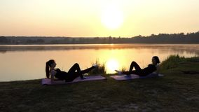 Two Slim Girls Lie on Mats, Raise One Leg Each, Smile, at Sunset. Two Young Women Lie on Mats in Front of Each Other, Raise One Leg up and Make Round Movements stock video