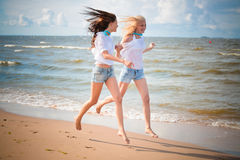 Two slim girls   running along the seashore Stock Photos