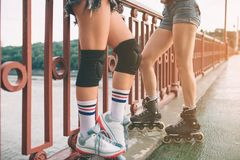 Two slim and sexy young women and roller skates. One female has an inline skates and the other has a quad skates. Girls Stock Images