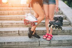 Two slim and sexy young women and roller skates. One female has an inline skates and the other has a quad skates. Girls Royalty Free Stock Images
