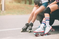 Two slim and sexy young women and roller skates. One female has an inline skates and the other has a quad skates. Girls Stock Photo