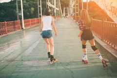 Two slim and sexy young women and roller skates. One female has an inline skates and the other has a quad skates. Girls Stock Image