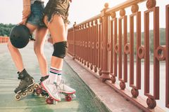 Two slim and sexy young women and roller skates. One female has an inline skates and the other has a quad skates. Girls Royalty Free Stock Photo