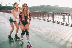 Two slim and sexy young women and roller skates. One female has an inline skates and the other has a quad skates. Girls Royalty Free Stock Photos