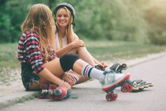 Two slim and sexy young women and roller skates. One female has an inline skates and the other has a quad skates. Girls Royalty Free Stock Image