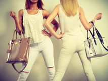 Two slim women in with leather bags handbags. Royalty Free Stock Photography