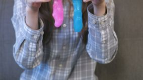 Two slimes pink and blue in woman`s hands. Playing with slime. stock video footage