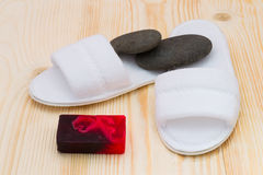 Two slippers and a bar of soap and stones. Items for foot care after work Stock Images