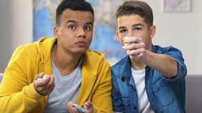 Two sloppy teenage boys watching movie on tv, eating popcorn, home entertainment. Stock footage stock footage