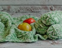 Two smal apple and thread for knitting lie on a plaid on a light background stock photo