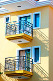 Two small balconies on the yellow house Stock Photos