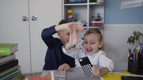 Two small beautiful children have fun and talk on the phone using a free internet network. The guys use the phone using. Two small beautiful children have fun stock video footage