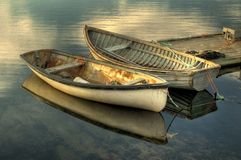 Two small boats. In Peggy's Cove, Nova Scotia. Strong reflections on glassy water surface of the bay royalty free stock image