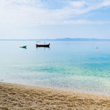 Two small boats in calm water near the sandy shore Stock Photography