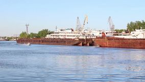 Two small boats float near big cargo barges. And passenger ships on river stock footage
