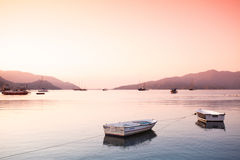 Two small boats tied with rope at Aegean sea bay Stock Photos