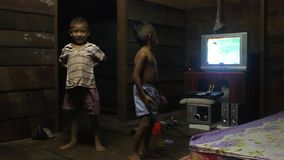 Two small boys. CENTRAL LAOS - AUGUST 21: Two small boys in Kong Lo village dance in front of a TV on August 21, 2012 in central Laos stock video footage