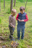 Two small boys lighting a fire in woodland Royalty Free Stock Photo