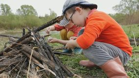 Two small boys make a fire on the picturesque banks of the river. Ultra HD 4K stock video