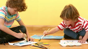 Two small boys painting pictures stock video footage