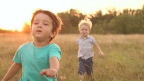 Two small boys run across the field at sunset. Two small boys run across the field at sunset, slow motion stock video