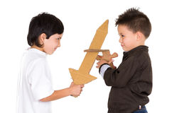 Two small boys simluating sword fight using toys Stock Images