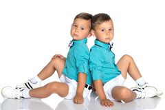 Two small boys sit on the floor back to back. Two cute little boys, brothers sit on the floor in a studio on a white background. The concept of a happy childhood Stock Photos