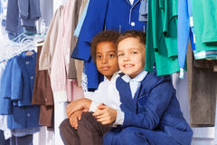 Two small boys sitting near clothes on the hangers Royalty Free Stock Images