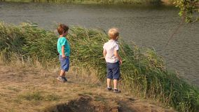 Two small boys throw stones into the lake. Two small active boys throw stones into the lake in the hot summer day. Two children play on the shore of the pond stock video