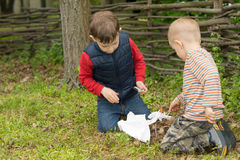 Two small boys trying to light a fire in a field Royalty Free Stock Images
