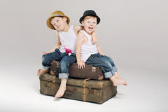 Two small brothers sitting on the suitcases Stock Photo
