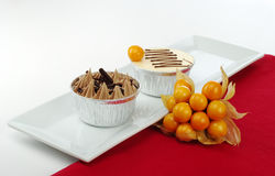 Two Small Cakes with Physalis. Two small cakes in tinfoil cups on rectangular white plate with physalis and red table mat (Selective Focus Stock Photography