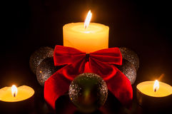 Two small candles around a bigger candle with christmas globes a stock photos