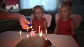 Two small charming and dressed twin sisters gathered near the festive cake with burning candles. Birthday in the family. Two small charming and dressed twin stock video footage