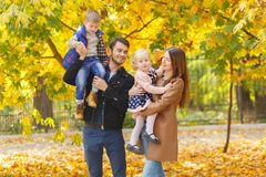 Two small children, a boy and a girl are sitting in their parents` hands in an autumn park. royalty free stock photography