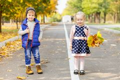 Two small children are walking in the autumn park. Royalty Free Stock Images